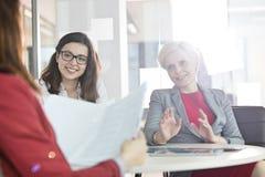Mogen affärskvinna med kvinnliga kollegor som i regeringsställning diskuterar på tabellen Arkivfoto