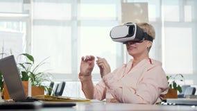 Mogen affärskvinna som försöker exponeringsglas för virtuell verklighet 3d på hennes arbetsplats arkivfilmer