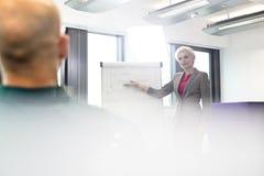 Mogen affärskvinna som ger presentation till den manliga kollegan i bräderum arkivfoton