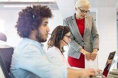 Mogen affärskvinna som hjälper den kvinnliga operatören med kollegan i förgrund på kontoret arkivfoto