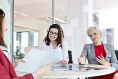 Mogen affärskvinna som i regeringsställning diskuterar med kvinnliga kollegor på tabellen fotografering för bildbyråer