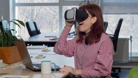 Mogen affärskvinna som tycker om genom att använda virtuell verklighethörlurar med mikrofon på hennes arbetsplats arkivfilmer