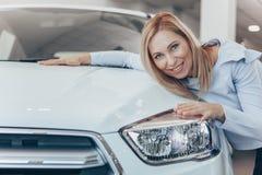 Mogen affärskvinna som väljer den nya bilen på återförsäljaren royaltyfri bild