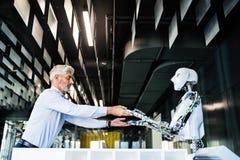 Mogen affärsman eller en forskare med roboten Arkivfoton