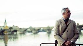 Mogen affärsman med hörlurar och smartphoneanseende vid floden i stad lager videofilmer
