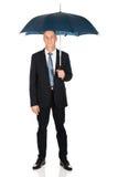 Mogen affärsman med paraplyet Royaltyfria Bilder