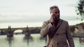Mogen affärsman med smartphoneanseende vid floden i staden som talar arkivfilmer