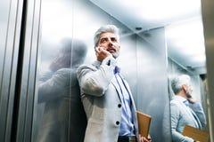 Mogen affärsman med smartphonen i hissen royaltyfria foton