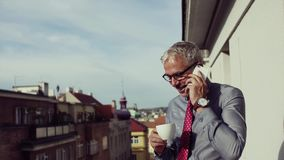 Mogen affärsman med smartphonen som står på en terrass i staden som gör en påringning stock video