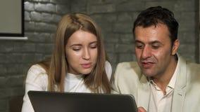 Mogen affärsman och hans ung kollega som arbetar på bärbara datorn royaltyfria bilder
