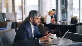 Mogen affärsman som använder bärbara datorn och smartphonen under affärslunch i kafé arkivfilmer
