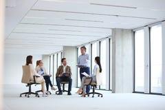 Mogen affärsman som diskuterar med kollegor som sitter på stol i nytt kontor arkivfoto