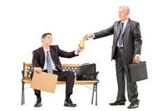 Mogen affärsman som ger några pengar till en tiggare Arkivfoto