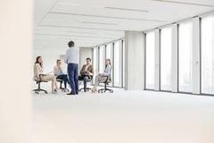 Mogen affärsman som har diskussion med kollegor som sitter på stol i nytt kontor arkivfoton
