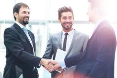 Mogen affärsman som skakar händer för att försegla ett avtal med hans partner och kollegor i ett modernt kontor royaltyfri foto