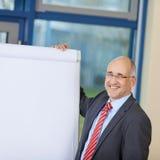Mogen affärsman Standing By Flipchart Fotografering för Bildbyråer