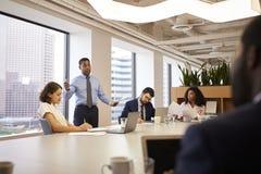 Mogen affärsman Standing Giving Presentation till kollegor i modernt öppet plankontor royaltyfria foton