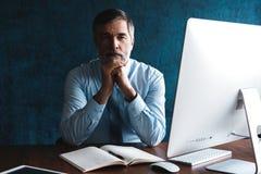 Mogen aff?rsman som ser och analyserar dokumentet i hans moderna kontor p? arbete arkivfoto