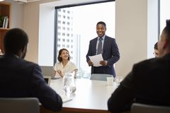 Mogen aff?rsman Standing Giving Presentation till kollegor i modernt ?ppet plankontor royaltyfri foto
