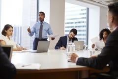 Mogen aff?rsman Standing Giving Presentation till kollegor i modernt ?ppet plankontor arkivbilder