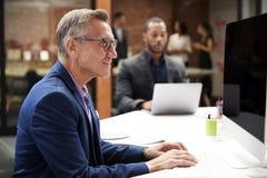 Mogen aff?rsman Working At Desk p? datoren i ?ppet plankontor med kollegor i bakgrund royaltyfri foto
