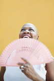 Mogen afrikansk kvinna med ventilatoren som ler Royaltyfria Foton