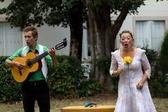 Mogen aktris som leker i en trädgård arkivbilder