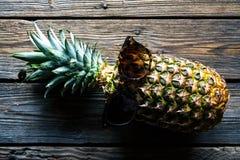 Mogen ananas med solglasögon på en vit trätabell Frukt natur, mat Fotografering för Bildbyråer