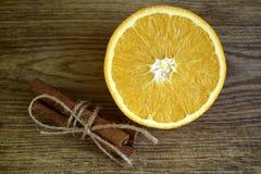 Mogen apelsin, kanelbruna pinnar på träyttersida arkivfoto