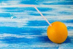 Mogen apelsin med röret för coctail på den blåa bakgrunden Sommardrinkar och sund livsstil royaltyfri bild