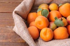 mogen aprikos i en påse på en brun träbakgrund Fotografering för Bildbyråer