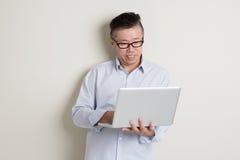 Mogen asiatisk man och IT-begrepp Royaltyfri Foto