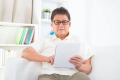 Mogen asiatisk man som använder minnestavlaPC Arkivbilder