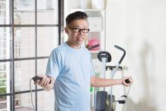 Mogen asiatisk man som gör hoppande over övning för rep Arkivbild
