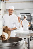 Mogen bagare Pouring Flour In som knådar maskinen arkivfoton