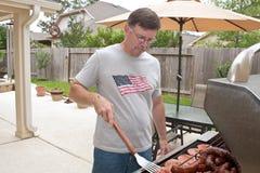 mogen barbecuing man Fotografering för Bildbyråer