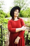Mogen brunettkvinna i den trädgårds- bärande hatten för gräsplan som ler, frie royaltyfri foto
