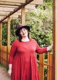 Mogen brunettkvinna i trädgårds- bärande hatt för gräsplan och att le, vänlig welkoming, slut för livsstilfolkbegrepp upp royaltyfria foton