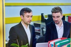 Mogen caucasian man som två arbetar i kontoret arkivbilder