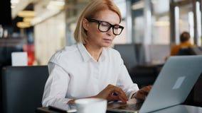 Mogen dam för företags chef som arbetar med bärbara datorn i kafét som skriver affärsmejl stock video