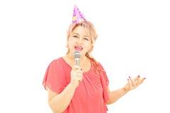 Mogen dam med partihatten som sjunger på mikrofonen fotografering för bildbyråer
