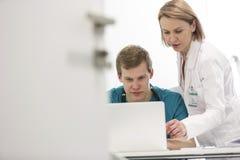 Mogen doktor som diskuterar med den unga sjuksköterskan över bärbara datorn på skrivbordet i sjukhus arkivfoton