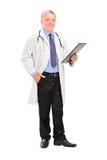 Mogen doktor som rymmer en clipboard Arkivfoto