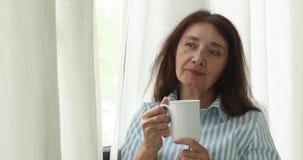 Mogen eftertänksam kvinna med kaffekoppen arkivfilmer