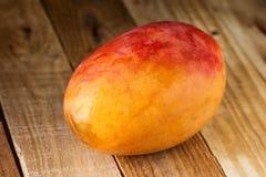 Mogen färgrik röd och gul hel mango på riden ut Wood bakgrund Bantar sund tropisk frukt för Smoothieingrediensen Royaltyfria Bilder