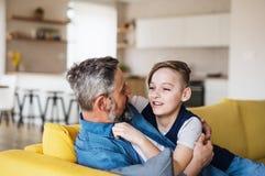 Mogen fader med den lilla sonen som inomhus sitter på soffan och att vila fotografering för bildbyråer