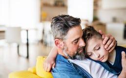 Mogen fader med den lilla sonen som inomhus sitter på soffan och att vila royaltyfria bilder