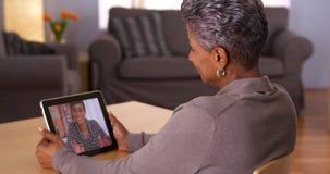 Mogen farmor som talar med sondottern på minnestavlan Arkivfoton