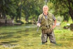 Mogen fiskare som poserar med metspöet i floden Royaltyfria Foton