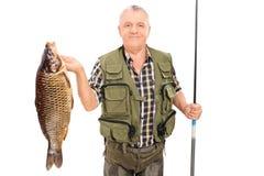 Mogen fiskare som rymmer den stora fisken och metspöet Royaltyfri Foto